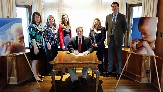 Kansas Gov. Brownback signs SB 95. With the governor are (l-r) the Kansans for Life Legislative team: Jeanne Gawdun, Kathy Ostrowski, and Jessica Basgall, J.D; and conferees Barbara Saldivar,State Director for Concerned Women for America, and Michael Schuttloffel, Executive Director, Kansas Catholic Conference.
